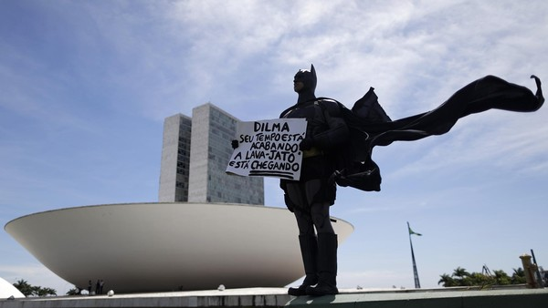 An anti-government demonstrator dressed as Batman stands in protest against corruption and against the induction of new members of the National Congress in Brasilia. February 1, 2015. Placard reads