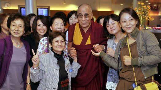Tiibetin hengellinen johtaja dalai-lama, Tenzin Gyatso, ja japanilaisia turisteja, jotka halusivat yhteiskuvaan dalai-laman kanssa Helsinki-Vantaan lentokentällä 18. elokuuta 2011.