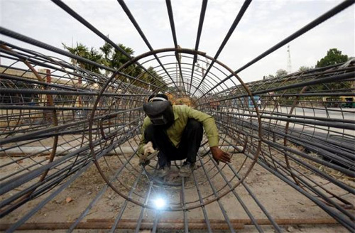 A worker welds iron rods at the Metro railway construction site in Kolkata.