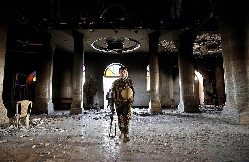 Каракош. Иракский военный перед первым воскресным богослужением в соборе Непорочного Зачатия