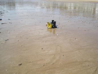 A group of children had abandoned their wellington boots on the beach and ran towards the water barefoot.