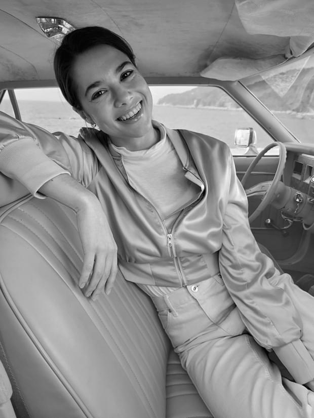 Woman sitting in the driver's seat, taken in Portrait Mode with High-key Mono effect applied.