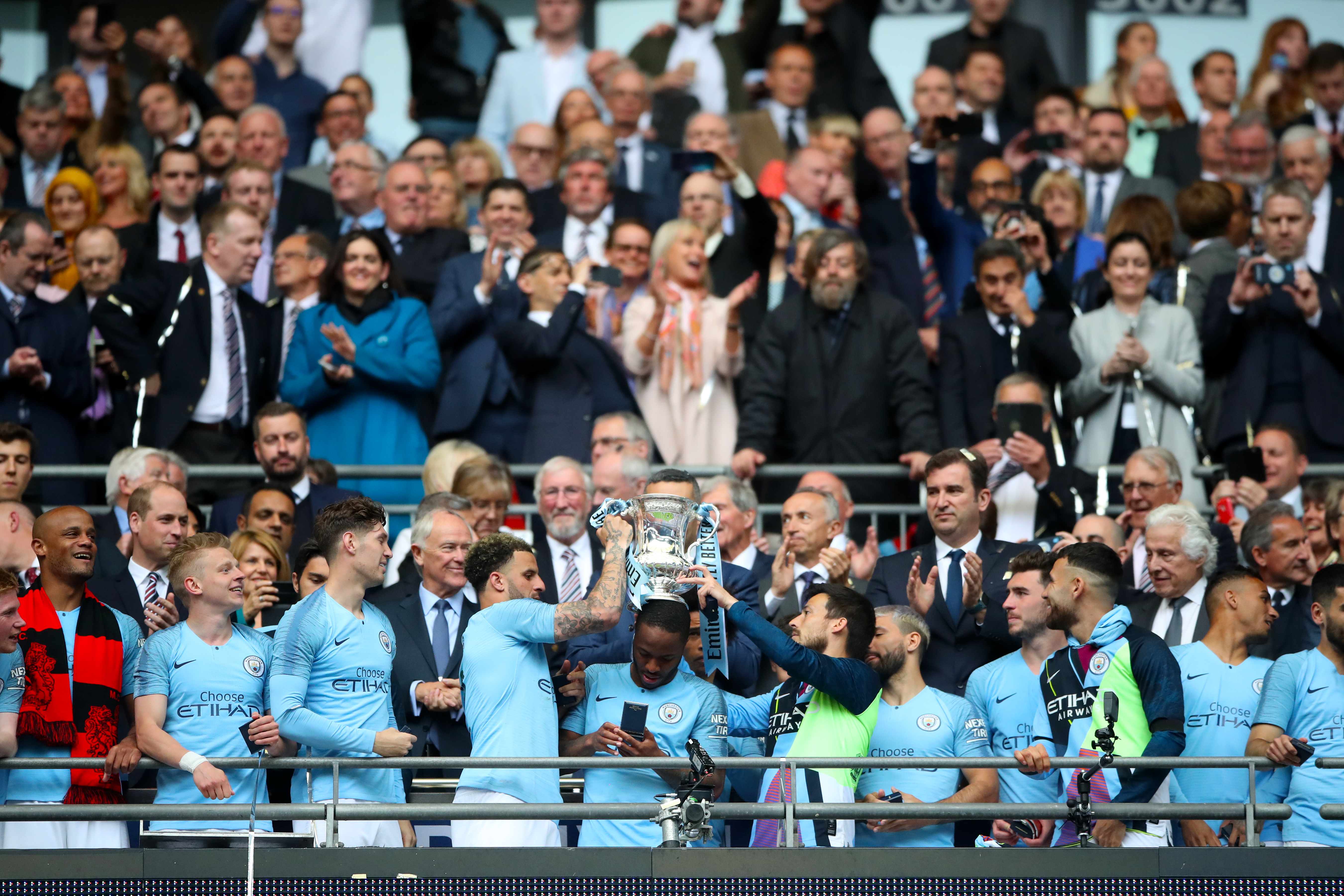 David Silva, centre right, lifts the FA Cup with Kyle Walker, centre left
