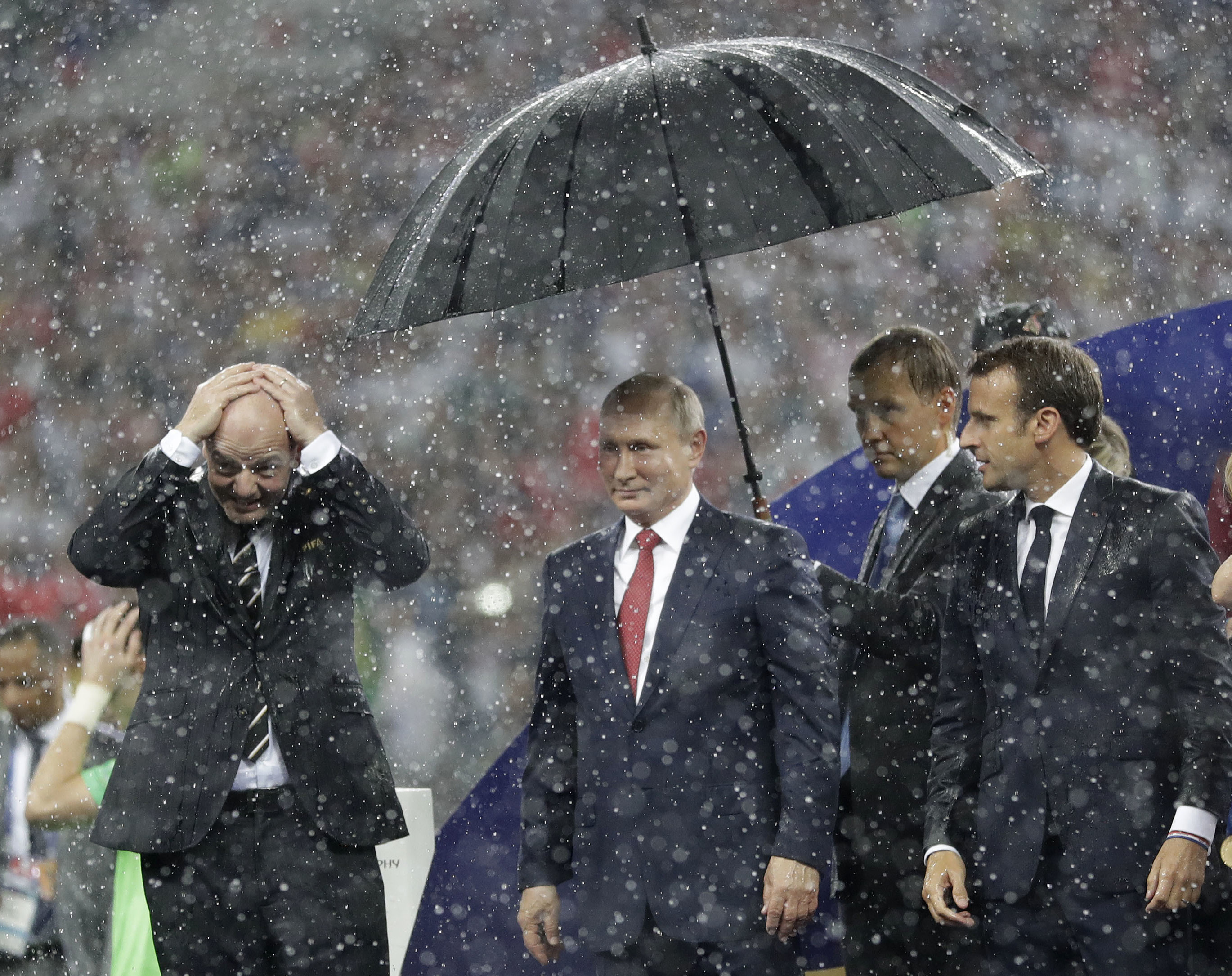 Vladimir Putin stands underneath an umbrella watched by French President Emmanuel Macron after the final match between France and Croatia at the 2018 World Cup  WATCH: Putin arrives for face-to-face talks with Trump in Helsinki 2