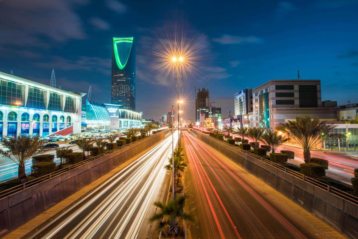 The Kingdom Tower, operated by Kingdom Holding, left, stands alongside the King Fahd highway, illuminated by the light trails of passing traffic, in Riyadh, Saudi Arabia, on Saturday, Jan. 9, 2016.