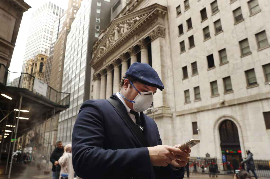 A man wears a protective mask as he walks past the New York Stock Exchange on the corner of Wall and Broad streets during the coronavirus outbreak in New York City, New York, U.S., March 13, 2020.