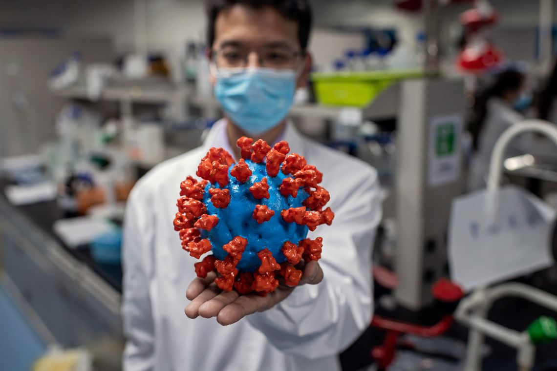 In this picture taken on April 29, 2020, an engineer shows a plastic model of the COVID-19 coronavirus at the Quality Control Laboratory at the Sinovac Biotech facilities in Beijing.