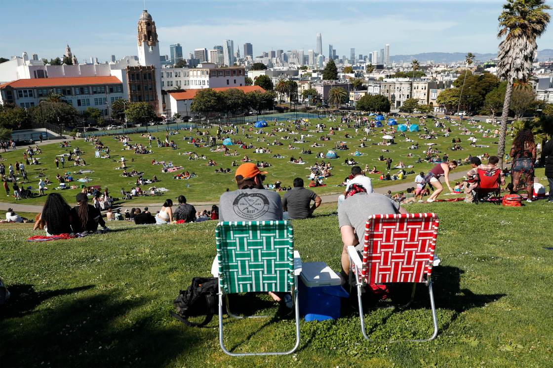Crowds - drawn by the sunny, warm weather - socially distance at Mission Dolores Park in San Francisco, Calif. to enjoy Memorial Day weekend, on Sunday, May 24, 2020.