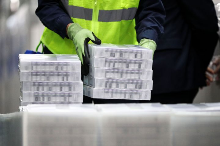 Pfizer employees handle containers of vaccine as U.S. President Joe Biden tours a Pfizer manufacturing plant producing the coronavirus disease (COVID-19) vaccine in Kalamazoo, Michigan, U.S., February 19, 2021.