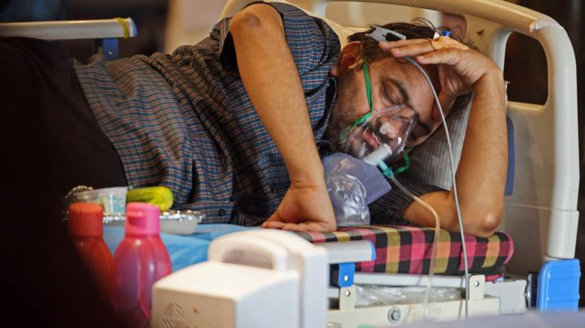 A Covid-19 coronavirus patient rests inside a banquet hall temporarily converted into a Covid care centre in New Delhi on May 10, 2021.
