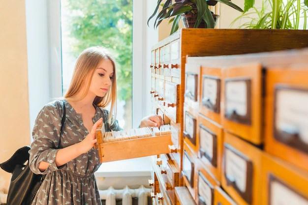 Adolescente buscando una tarjeta en el catálogo de la biblioteca Foto gratis