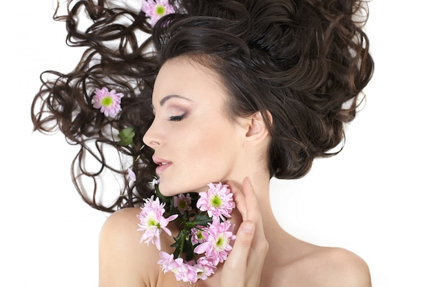 Bastante hermosa niña acostada con flores brillantes en su cabello maquillaje brillante aislado en blanco Foto gratis