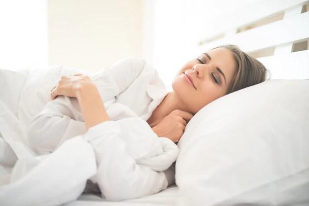 Hermosa mujer joven durmiendo en la cama Foto gratis