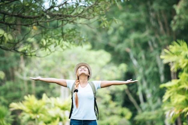La mujer feliz joven con la mochila que levanta la mano goza con la naturaleza. Foto gratis