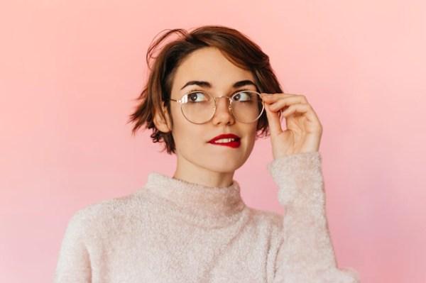 Mujer guapa pensativa tocando gafas Foto gratis