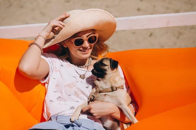 Mujer con perro en la playa en un colchón de la piscina Foto gratis