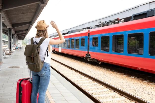 Mujer saludando al tren desde atrás Foto gratis