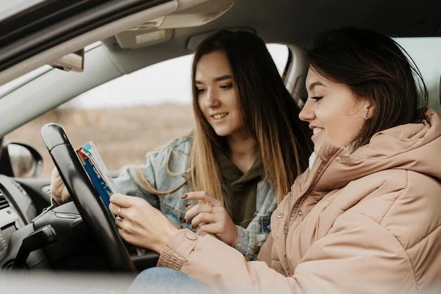 Mujeres hermosas que comprueban vista lateral del mapa del viaje Foto gratis