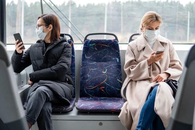 Mujeres jóvenes en transporte público con mascarilla quirúrgica Foto gratis