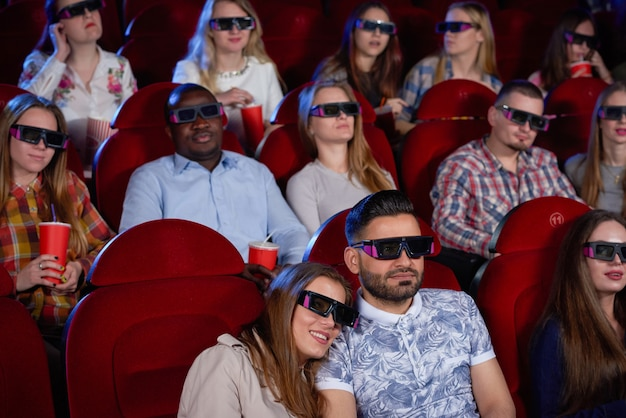 Pareja hombre árabe y mujer morena sentados juntos en el cine, abrazar y ver comedia. Foto Premium