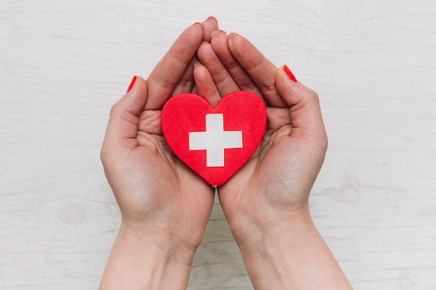 Recortar las manos sosteniendo el corazón con la cruz Foto gratis