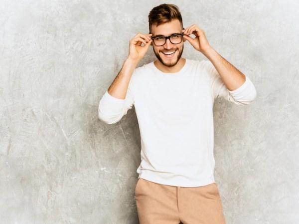 Retrato del modelo sonriente hermoso del hombre de negocios del inconformista que lleva la ropa blanca casual del verano. Foto gratis