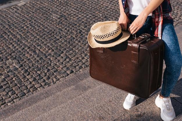 Sección baja de una mujer que lleva una bolsa de equipaje marrón con un sombrero de pie en la escalera Foto gratis