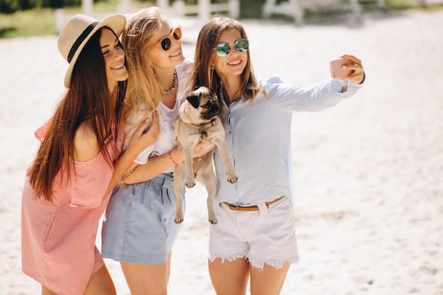 Tres mujeres en la playa con perro pequeño Foto gratis