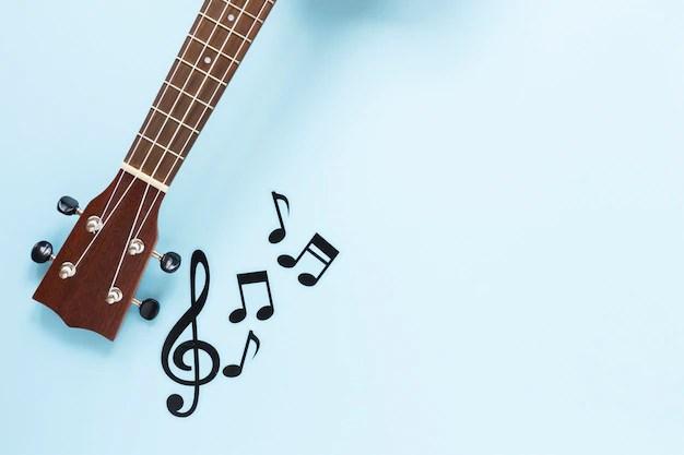 Braço de guitarra de vista superior com notas musicais em fundo azul para controlar ansiedade na quarentena