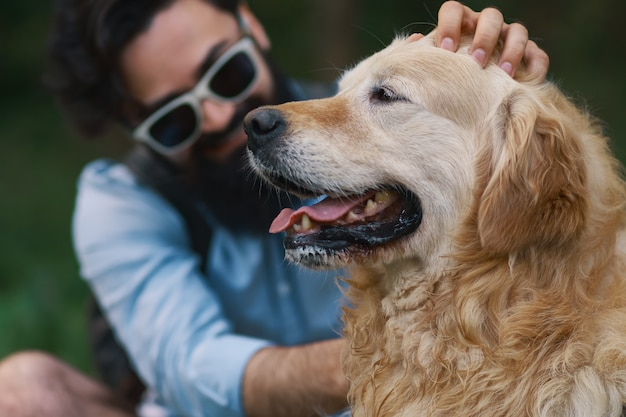 Homem de barba e óculos fazendo carinho no seu cachorro