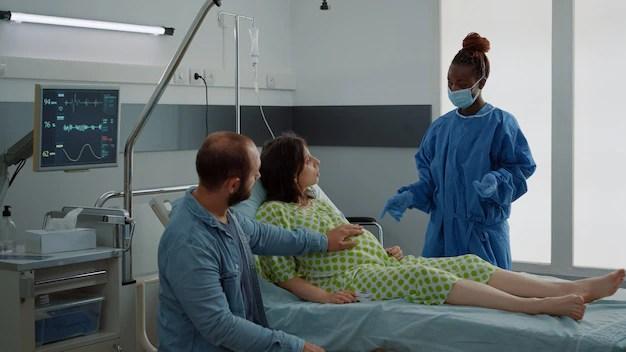 casal-caucasiano-esperando-bebe-na-maternidade-do-hospital-mulher-gravida-sentada-na-cama-falando-com-a-enfermeira-afro-americana-e-o-jovem-marido-assistencia-medica-para-parto_482257-9359 Corrimento Marrom: O que isso significa?