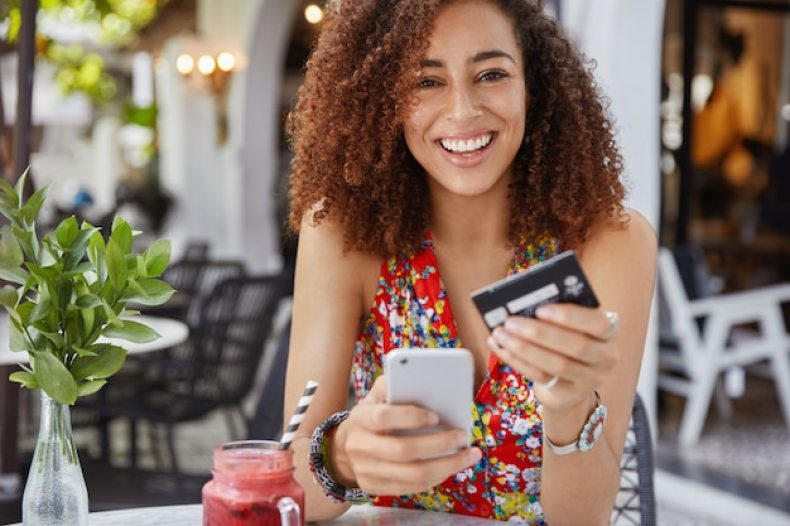na imagem uma mulher jovem feliz e sorridente com penteado afro, usa um celular moderno e um cartão de crédito para fazer compras online | O Guia do Cartão de Crédito