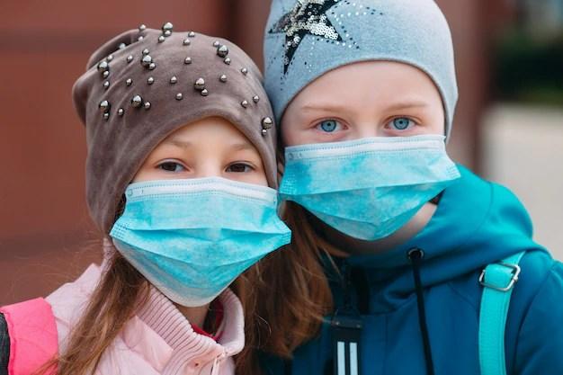 Pré-adolescentes com máscaras e toucas