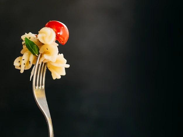 Garfo com macarrão, tomate cereja e tempero verde em fundo preto