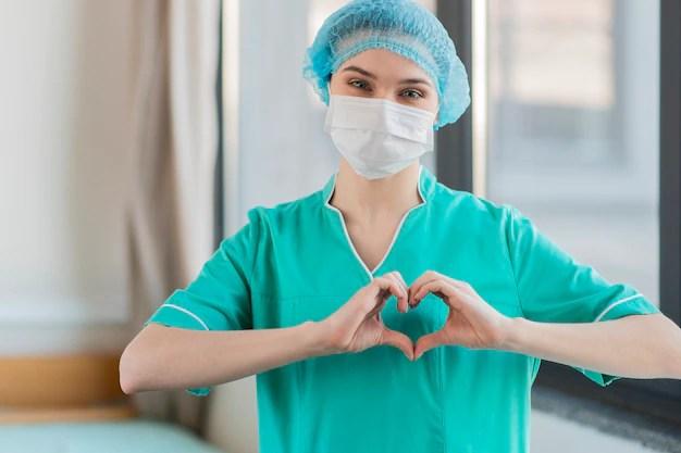 Enfermeira com forma de coração de mãos Foto gratuita