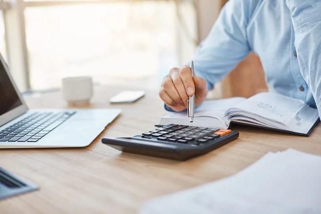 Feche acima do detalhe do contador sério profissional sentado no escritório de luz, verificando os lucros das finanças da empresa na calculadora Foto gratuita