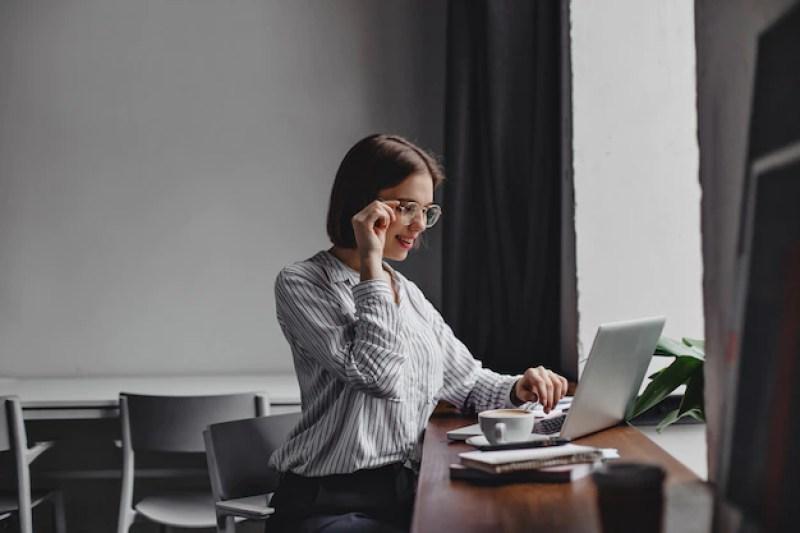 mulher de negócios de cabelos curtos de óculos e blusa branca, sentado no local de trabalho e trabalhando no laptop | Entenda o Projeto de Lei  da Reforma Tributária