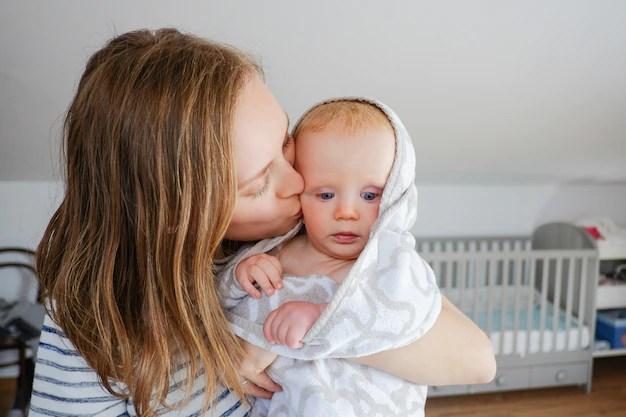 Mãe beijando bebê que está com frio no seu colo
