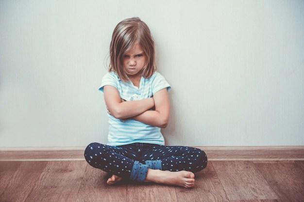 Linda menina sentada no chão com ansiedade infantil