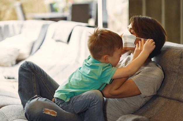 Mãe com máscara em sofá com criança durante quarentena