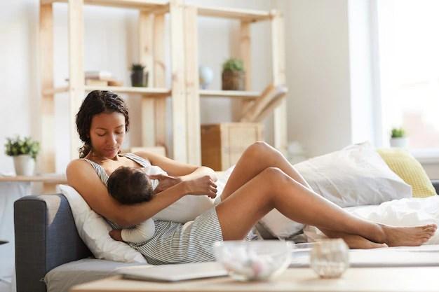 Mãe negra amamentando bebê mamadeira
