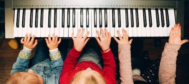 Mãos de crianças tocando piano elétrico. instrumento musical nas mãos das crianças Foto Premium