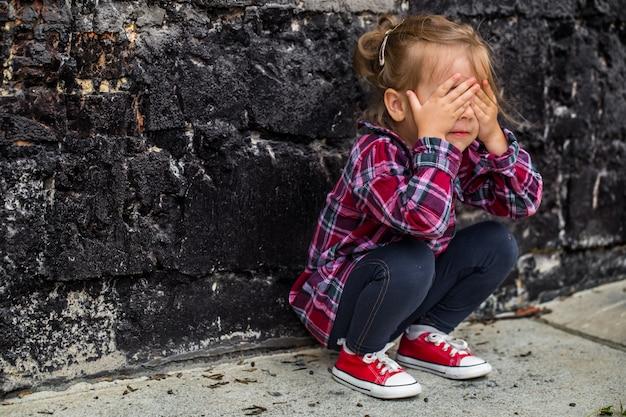 Menina agachada no chão escondendo rosto com as mãos