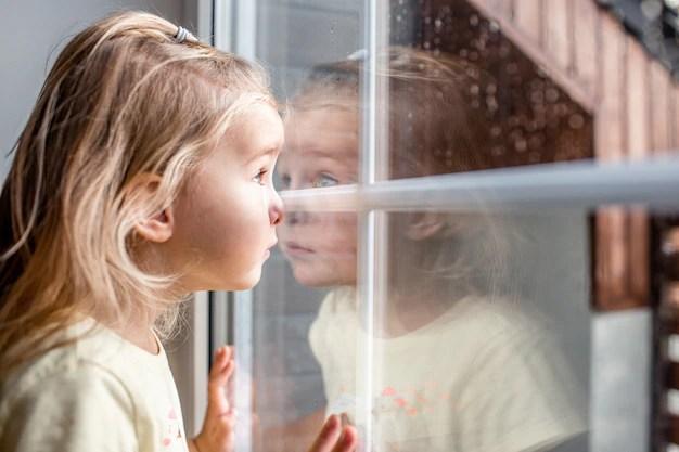 Menina em quarentena pelo coronavírus olhando a rua pela janela