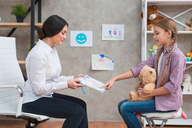 Menina, sentando, com, urso teddy, apontar, a, desenho, papel, mostrado, por, dela, femininas, psicólogo Foto gratuita
