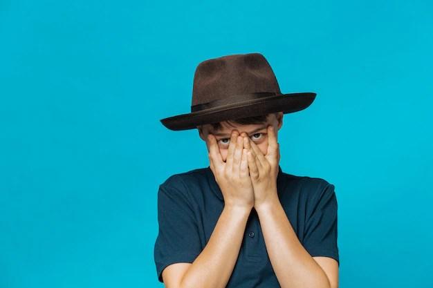 Menino tímido com chapéu em fundo azul com mutismo seletivo