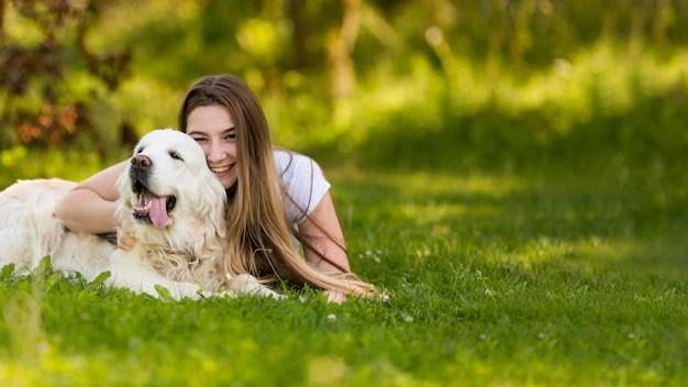 Cadela no cio sendo abraçada por sua tutora em parque