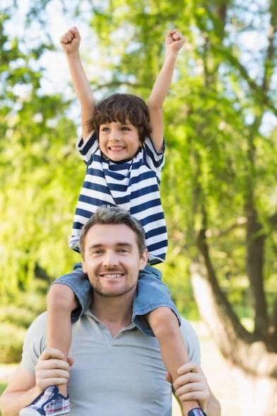Pai carregando um filho feliz nos ombros no parque | Foto Premium