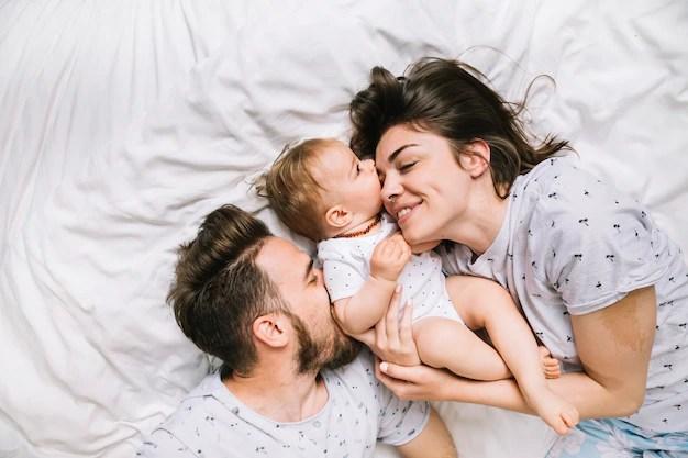 Família com bebê deitados na cama