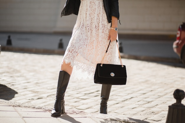 Pernas de uma jovem mulher bonita com botas andando na rua com roupa da  moda, segurando bolsa, vestindo jaqueta de couro preta e vestido de renda  branca, estilo primavera outono   Foto